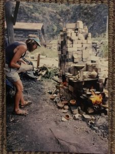 Man removing a pot from kiln with tongs